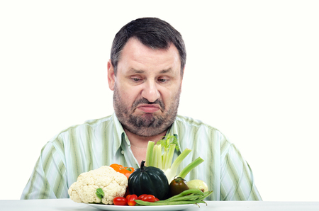 unwillingness: Horizontal portrait of middle aged bearded man does not like a fresh vegetables