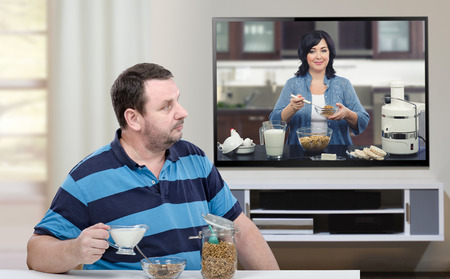 big screen tv: Man has breakfast and looking at big TV screen. In the screen, nutritionist is making a healthy breakfast in kitchen with muesli, diet rice cakes, white cheese, eggs and milk Stock Photo