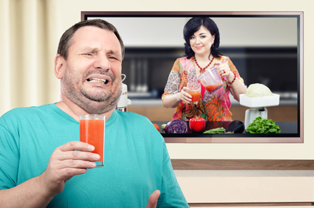 panicked: Portrait of panicked man is holding glass of detox drink on the background of dietitian on the big TV screen Stock Photo