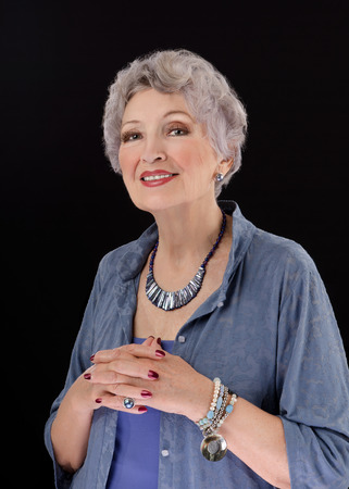 grey haired: Classy 76-year-old woman with abalone paua shell stick bar beads. Grey haired woman is wearing blue blouse with buttons and posing on black background