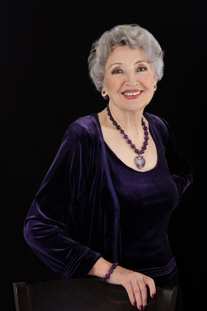 shrug: Sspectacular 76-year-old woman with amethyst bead necklace and bracelet. Grey haired woman is wearing violet velvet shrug Stock Photo