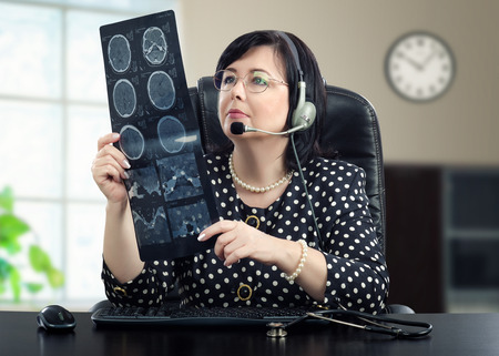 Telemedicine doctor in headphones is looking at x ray picture of brain carefully