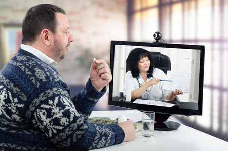 Bearded man in Scandinavian sweater takes pill during virtual doctor session