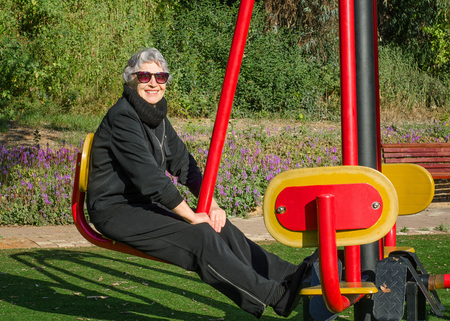 enhances: Old woman in sunglasses tries out knee bender machine in her local park. Grey-haired woman in black sport suit is working out at outdoor gym. She enhances flexibility of her waist and legs