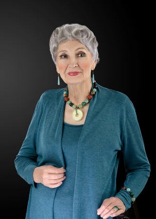 shrug: Portrait of spectacular 76-year-old woman wears multi colored semiprecious stone beads necklace with donut pendant and bracelet. Grey haired woman is clothed in old turquoise shrug set Stock Photo