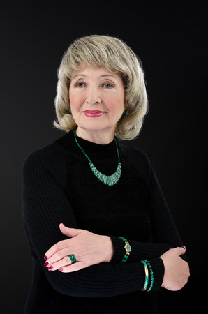 turtleneck: Portrait of stunning 76-year-old woman wears malachite stick bar beads, bracelets, watch and rings. She crosses her arms on black turtleneck shirt. Stock Photo