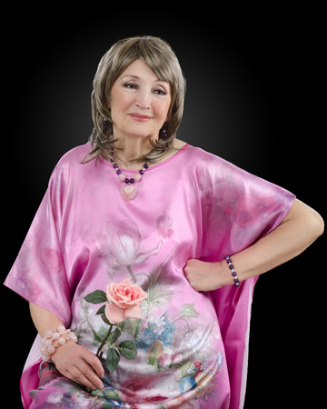 peignoir: Half-length portrait of pensive 76-year-old woman dresses in pink silk robe and holds pink rose with right hand. In addition, she wears blonde wig, amethyst rose quartz bead necklace and bracelets