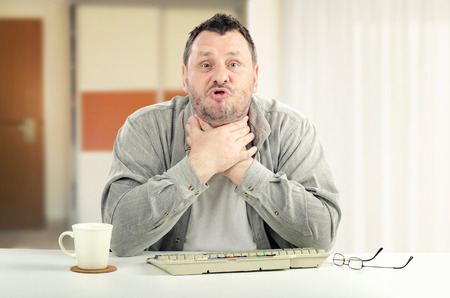 stressing: Portrait of middle-aged man is reached at the point of stressing out.  The man is creaming with hands on his neck. He sits at white desk.