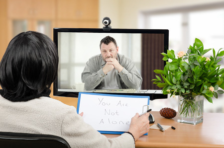 Middle aged man talks with psychotherapist via online video chat. He looking depressed. Black-haired woman holds written message for him - You are not alone.