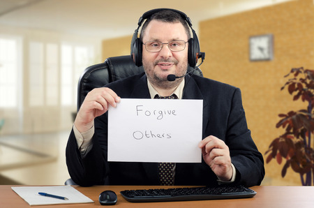psychiatrist: Portrait online psychiatrist.  Middle-aged man in black suit sits at the desk and holds written message Forgive Others. He wearing a headset cause he works on-line psychiatrist