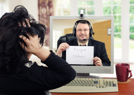 agitated: Depressed woman is exceedingly agitated at first encounter with virtual psychotherapist.  The patient holds her head in her hands. Middle-aged glasses psychiatrist looks and listens her on monitor