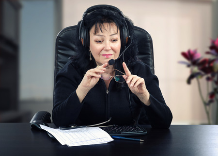 telecommute: Portrait of mature physician is sitting at black wooden desk. Black haired woman wears headset because works online. She holds glasses in her hands. Stock Photo