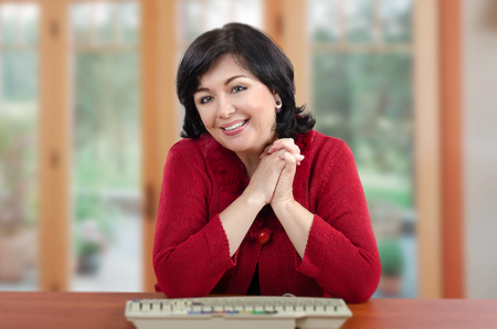 knitted jacket: Portrait smiling middle-aged black-haired woman in red knitted jacket sits at the wooden desk Stock Photo