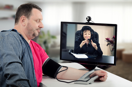Virtual therapist carefully watches blood pressure figures of her patient. She wears headset because works online