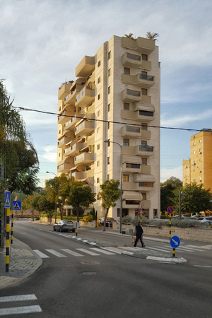 zebra crossing: Rishon LeZion, Israel - January 30, 2016: Nine-story residential building with contemporary glass balconies. Unidentified man walking with dog on zebra crossing Editorial