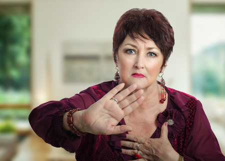 Mature woman asking dont take her photo. Woman in dark brown wig shows rejected gesture by right hand and looks at the camera irritatingly Stock Photo