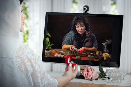 diviner: Clairvoyant uses energy of semi-precious gemstones for charging wedding rings during on-line video session in internet for bride in white dress Stock Photo