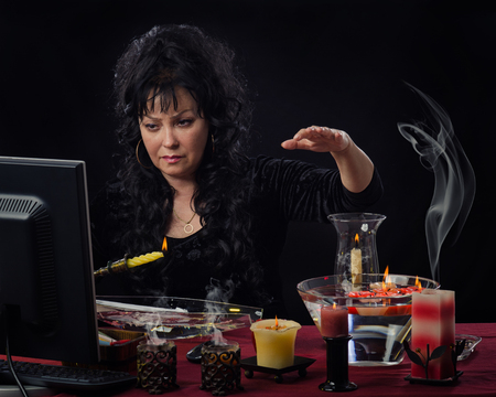 scrying: Mature female fortuneteller holds yellow burning candle upright over the water in front of monitor. Wax will start dripping onto the water soon