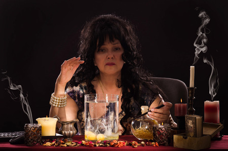 psychic reading: Aged fortune teller is reading a shapes of whites in jar with water. Black haired psychic is doing egg divination or oomancy