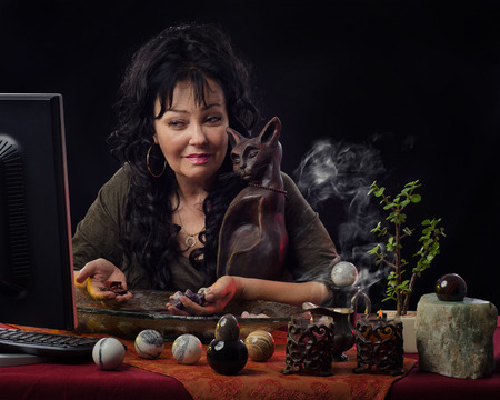 psychic reading: Fortuneteller predicts future on-line with semi-precious gemstones. The mature black haired diviner sits at the desk surrounded by different jasper spheres, smoking candles and looks at the monitor