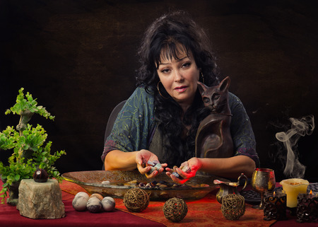 psychic reading: Gorgeous mature female fortuneteller with cat statuette sitting at the desk. She holds some wet stones in hands and looks at camera