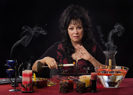 scrying: Mature female magical practitioner holds burning candle over long glass bowl with water. The fortuneteller allows the candle wax to drip into the water Stock Photo