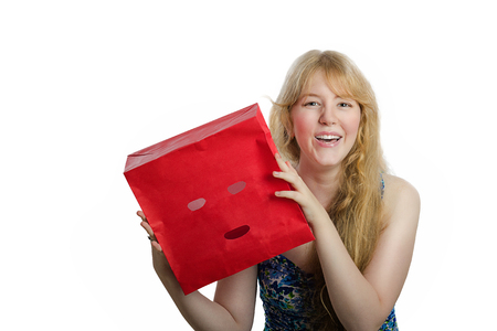 openness: Young blonde girl has just removed red paper bag from her head and laughs. Cheerful long-haired girl wants to be open Stock Photo