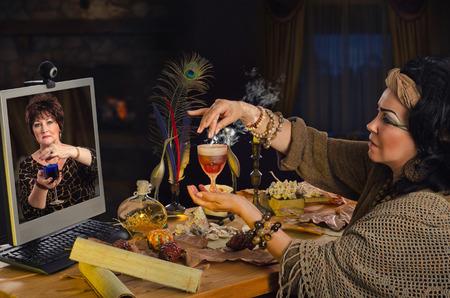 faire l amour: Sorcière enseigne en ligne comment faire l'amour potion. Le psychique tient verre brun clair de la boisson et crédite avec de la poudre magique. apprenant d'âge mûr dans le moniteur répète soigneusement