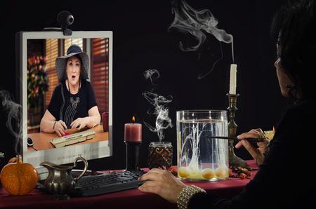 psychic: Psíquica está haciendo adivinación de huevo en línea. Adivino está leyendo un formas de claras de huevo en el vaso de vidrio para mujer de mediana edad con la expresión facial sorprendida en el monitor Foto de archivo