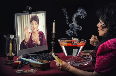 Fortuneteller starts reading a clients right hand on the monitor during on-line session. Psychic tensely looks at the shapes and lines of mature womans palm. Customers face looks a little bit scared