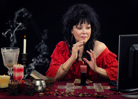foretell: Stunning mature Gypsy woman predicting future online with fortune telling cards. Black-haired woman looking at monitor during live online session with her client Stock Photo
