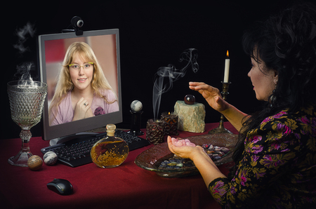 diviner: Modern witch teaches young blonde girl how to attract love with rose quartz during on-line video session. Simple long haired girl looks intently to clairvoyant