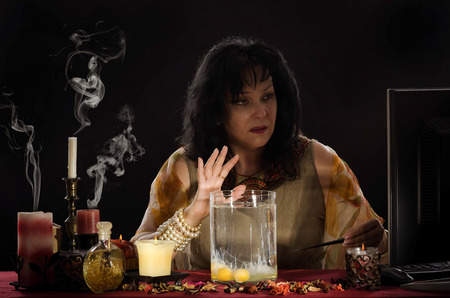 psychic reading: Fortune teller reading a shapes of egg whites into jar with fresh water. Black haired seer performing online in front of monitor