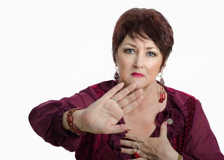 invade: Woman inquires stay away from her personal space. Posed portrait of mature woman shows reject gesture and wary looks at the camera