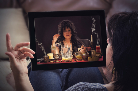 Woman on a sofa with tablet computer has online conversation with psychic doing egg divination. Black haired fortune teller is reading a shapes of egg whites in  touchscreen