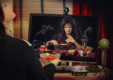 diviner: Woman in trance has internet video session with fortuneteller. The psychic holds yellow burning candle over the water and looks at woman in monitor Stock Photo