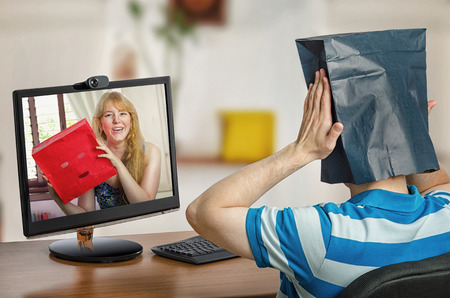 he laughs: During online video calling, young girl has just removed red paper bag from her head. Blonde girl laughs and asks young man take his bag off. He starts doing it Stock Photo