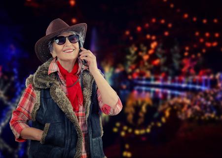 Smiling stunning senior cowgirl in sleeveless sheepskin jacket calls on mobile phone on outdoors Christmas blurry decoration background Stock Photo