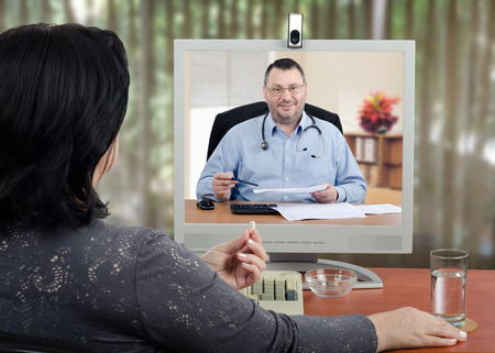 Mature woman holds a pill by hand and looks at online doctor. Patient prefers take a pills under telehealth control Stock Photo
