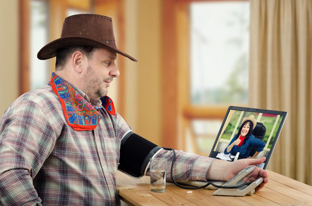Farmer suffers hypertension. Cowboy measures his blood pressure. Online female rural doctor gives thumb up and looks at him from monitor