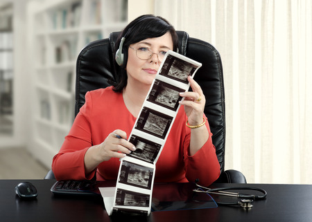 Female online doctor in headset sitting at the desk exams at ultrasound mammogram results attentively