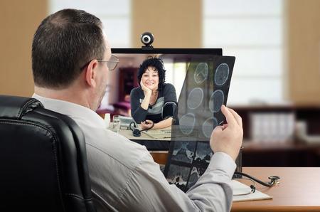 온라인 신경 외과의 사는 동시에 자신의 혈압을 측정하는 여성 환자의 뇌 질환을 온라인으로 진단합니다.