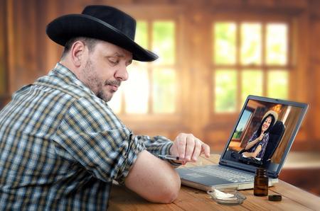 inyeccion intramuscular: ? Owboy en el sombrero negro quiere dar la auto-inyección intramuscular en el brazo, pero mantiene la jeringa mal. médico rural en línea en el monitor corrigiéndolo Foto de archivo