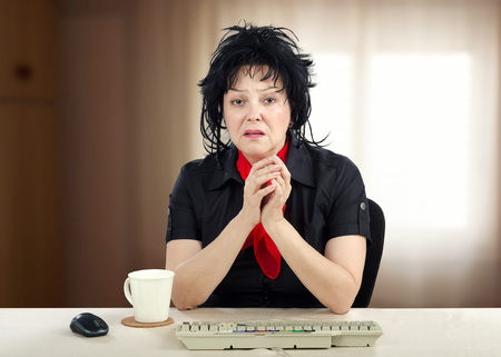 Portrait of frightened middle aged woman sitting at the desk and looking at the camera