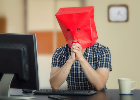 Real introverted young guy in red paper bag over head is frightened at first time online dating