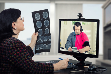 telecommute: Sitting in front of monitor telehealth doctor attentively looks at mans brain x-ray results while he takes blood pressure