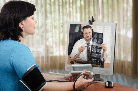 her: Telehealth online patient has just taken her blood pressure and shows results to doctor in her monitor which carefully looking at  brain x ray picture Stock Photo