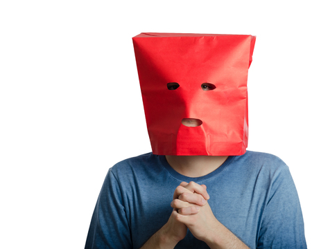 clench: Introverted young man with clenched hands wears red paper bag over head because he is lacking in confidence Stock Photo