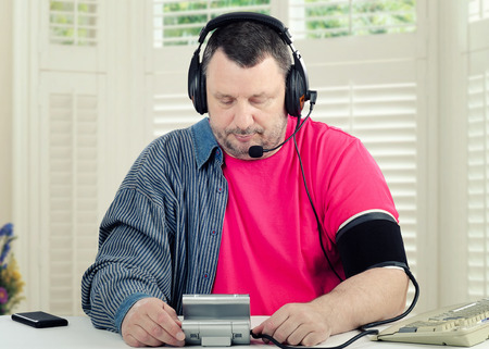Sitting at the desk male telemedicine patient monitors his blood pressure with a blood pressure gauge in his home Stock Photo