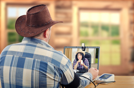 Sitting farmer takes blood pressure during internet session with virtual rural doctor in laptops monitor